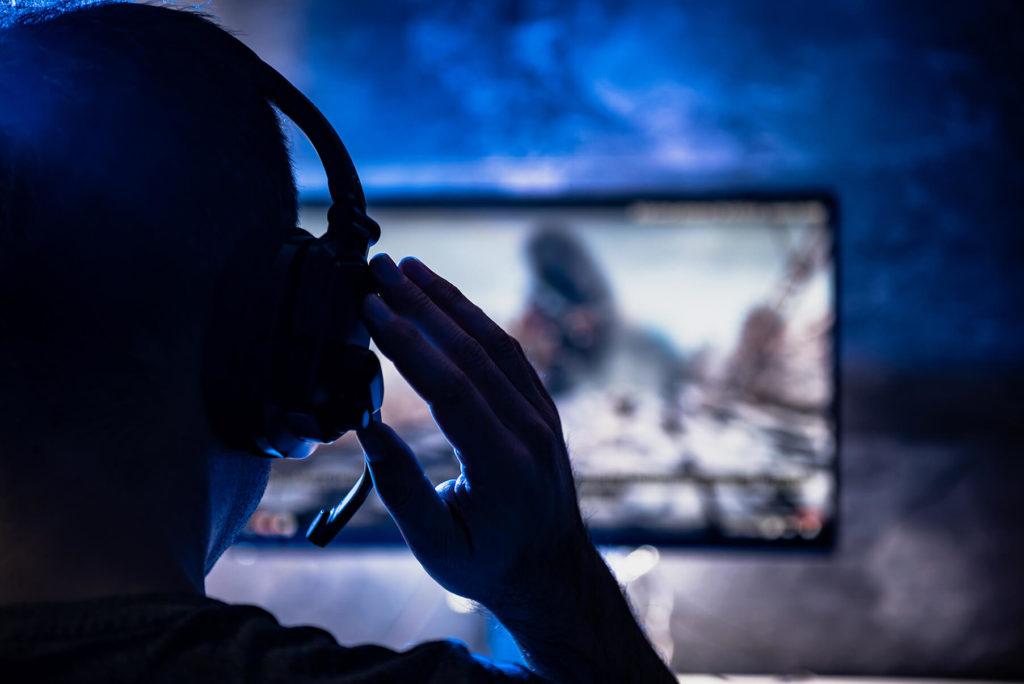 Gamer ser på skjerm og tar på seg headset
